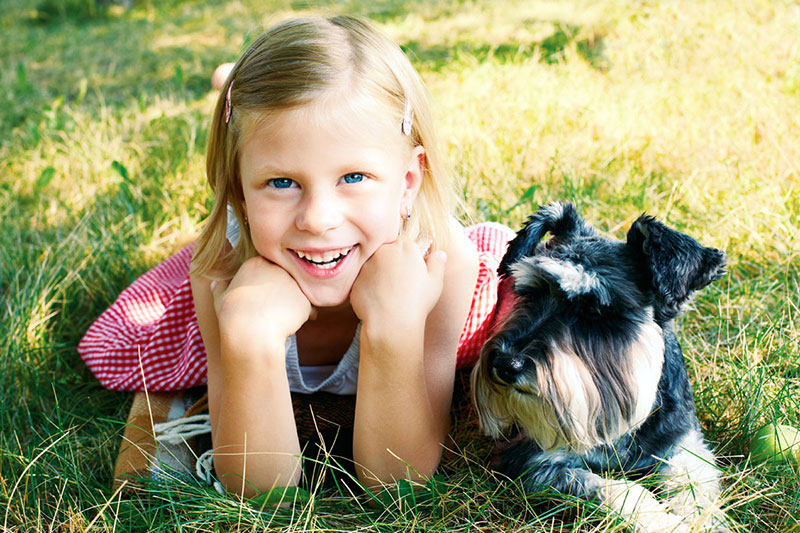Smiling girl, posing with old dog on lawn photo